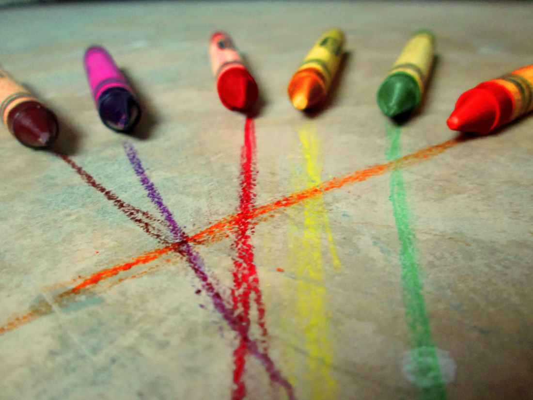 six crayons on gray concrete floor