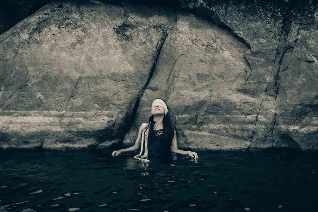 woman in blindfold wearing black top on body of water while leaning on a rock