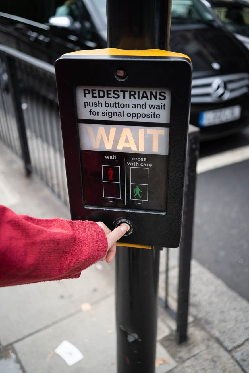 photo of person pressing the button of pedestrian box